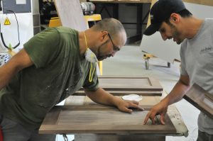 Chris and one of his staff sharing their views about  a door that has just been power sanded.