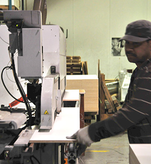 A Cutler staffer feeds a panel through the bandsaw.