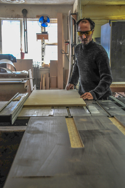 In the North Montreal production shop, a panel gets run through the table saw.