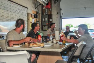 In this family business, the entire staff is treated like family. Every summer Friday is BBQ lunch day. After barbecuing the burgers himself,  Art Enns (at the head of the table) shares a meal and conversation with staff including his son Steven (third from left).